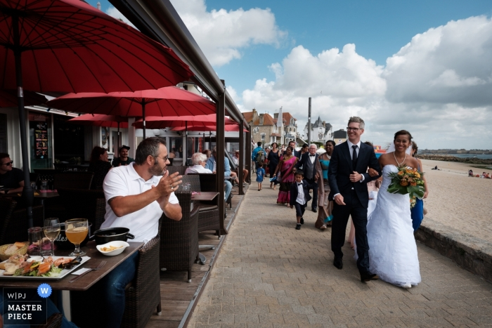 Morbihan wedding photojournalism image of a couple walking past diners at an outdoor café in Brittany