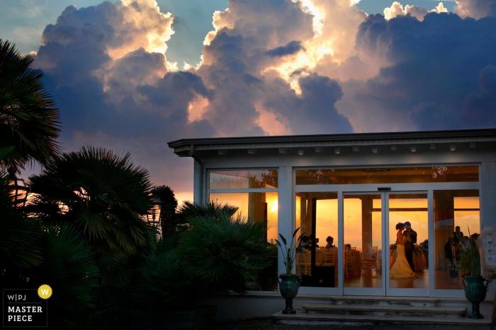 Reggio Calabria buitenkant huwelijksshoot met een paar binnen dansen met een prachtige zonsondergang en fantastische wolken buiten