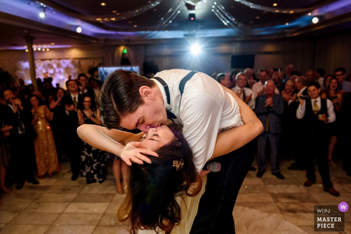 Picture of a couple dipping and kissing on the dance floor by a top Anaheim, CA wedding photographer