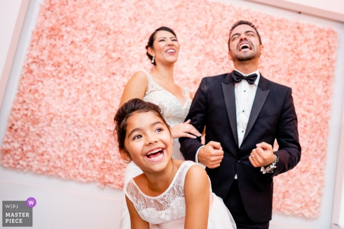 L2 Lounge, Washington DC wedding photo of bride, groom and flower girl laughing during reception.