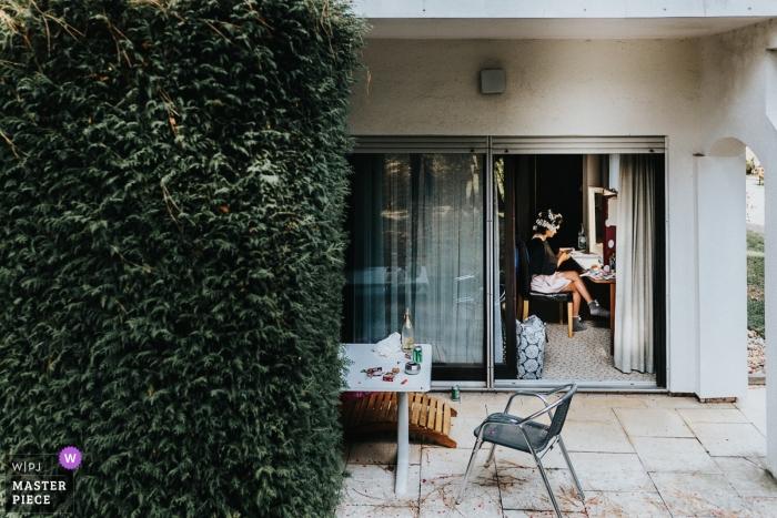 Fotojornalismo de casamento no Landhotel Waldhaus - noiva se preparando perto de uma parede de Hera