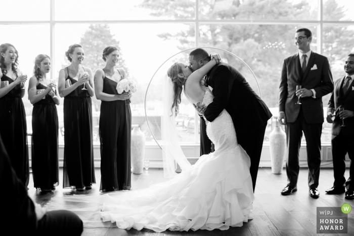 Cérémonie rétroéclairée Image d'un couple s'embrassant et plongeant, par un photographe de mariage de haut niveau à Providence