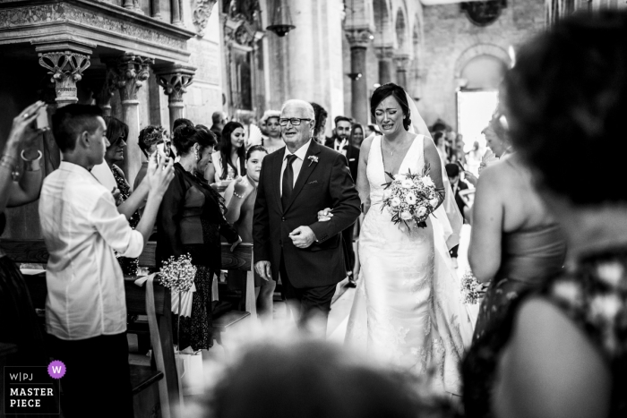 Immagine di una sposa che diventa emotiva mentre entra in chiesa con suo padre, da un top fotografo di matrimoni in Puglia