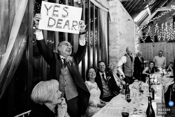 """Pátio do país de Kingston, Wareham, fotografia BRITÂNICA do casamento do convidado que sustenta """"sim o sinal handmade caro"""" na recepção."""