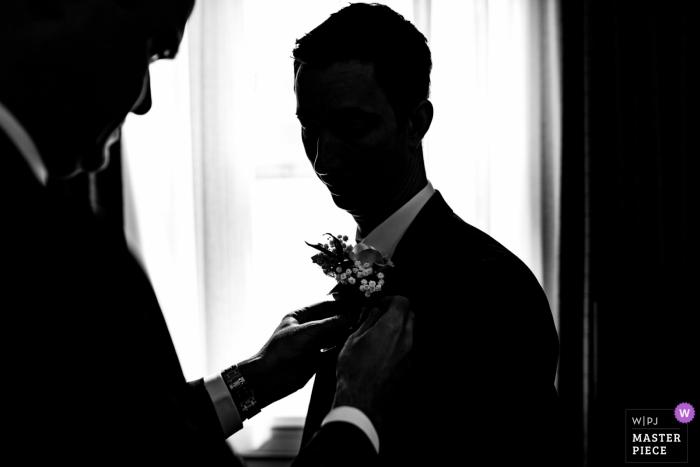 Photographie de mariage de Latimer Estate du marié obtenant un boutineer attaché à la mode.