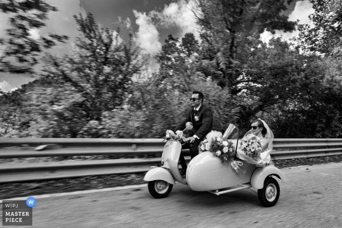 Hochzeits-Shooting mit Reggio Calabria-Paaren, die in einem Nebenauto Moto-Roller / Moped / Motorrad fahren