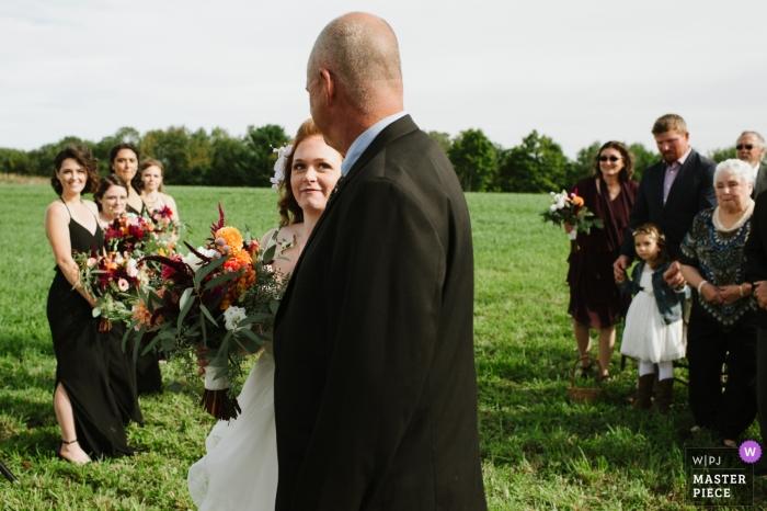 Une mariée regarde son père alors qu'elle marche dans l'allée lors de la cérémonie de son mariage | Des yeux d'amour et de remerciement