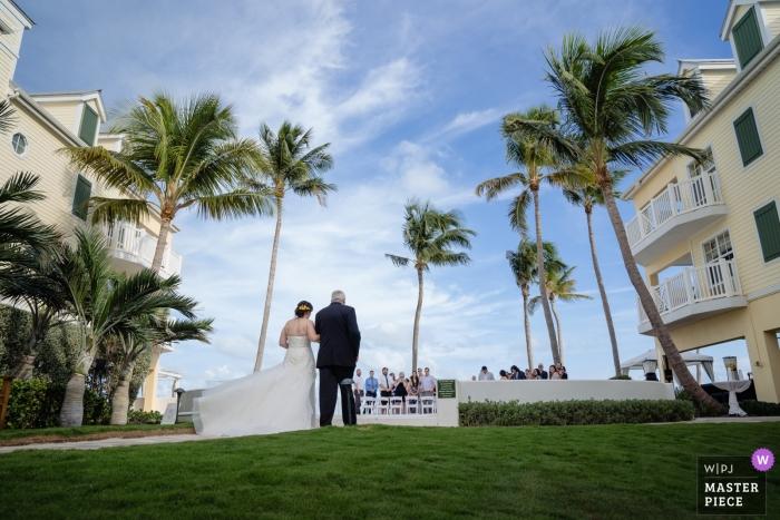Plus au sud sur la plage, photographie de mariage à Key West de la mariée et de son père marchant dans la cérémonie en plein air sous des palmiers.