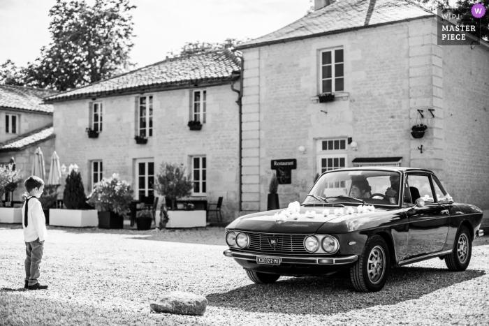 Przyjazd samochodu oblubieńca przed zniewolonym małym chłopcem - Domaine du Greffier w Granzay-Gript FRANCJA - Fotograf ślubny w La Rochelle