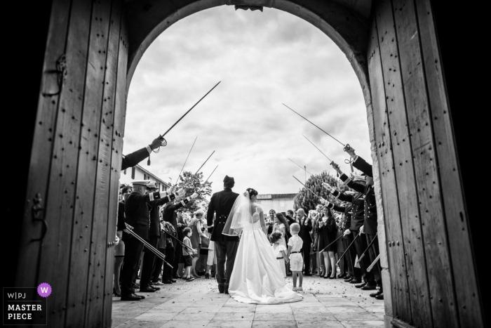 La novia y el novio son recibidos por un seto de honor de la medicina militar después de su ceremonia religiosa - Fotografía de bodas en La Rochelle - La salida de la iglesia de los recién casados bajo una guardia de honor