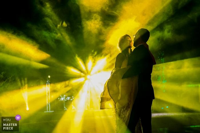 Los novios bailan con luces de DJ amarillas y verdes en su boda en Mascota, Jalisco. Mexico