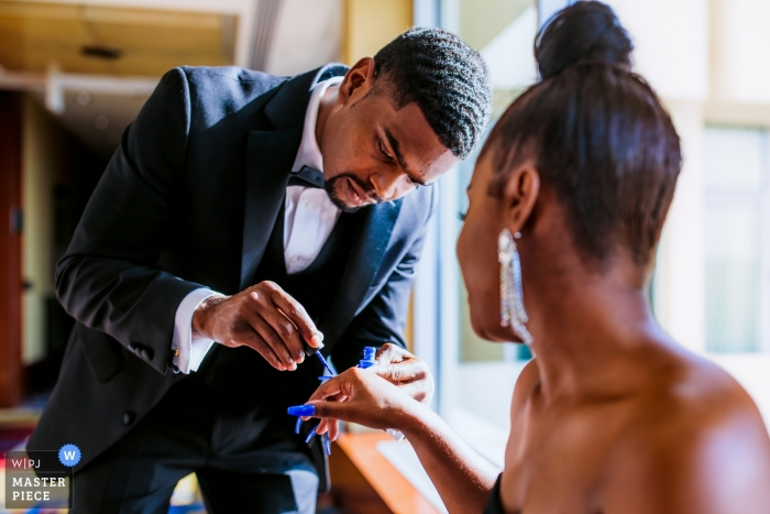 Picture of a groom painting bride's nails by a top Arlington, VA wedding photographer
