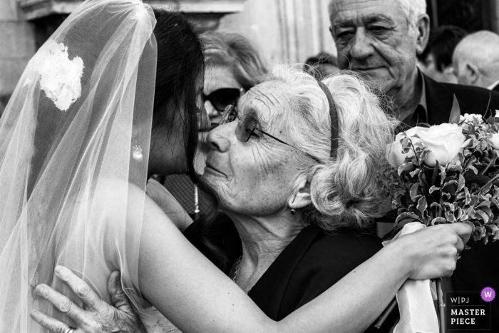 Sicilia-Hochzeitsfotografie einer Braut, die eine ältere Frau umarmt, während sie ihren Blumenstrauß der Blumen hält