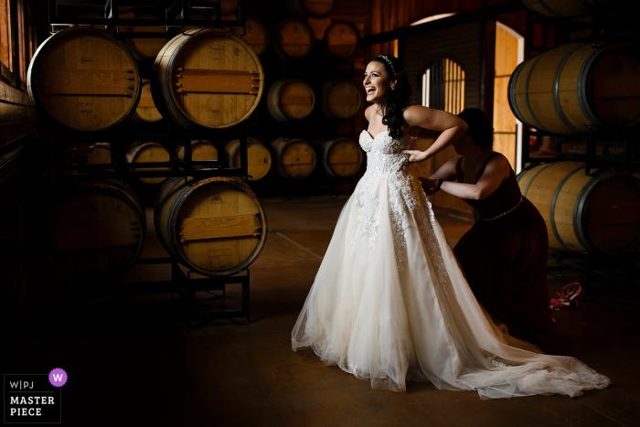 Panna młoda śmieje się, zakładając sukienkę w pokoju Barrell przed jej ślubem Krzywego Willow Farms w Larkspur, Colorado