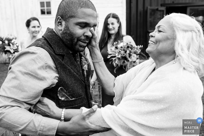 Wedding photojournalism in Belgrade, Montana - Mom wipes away a tear after ceremony