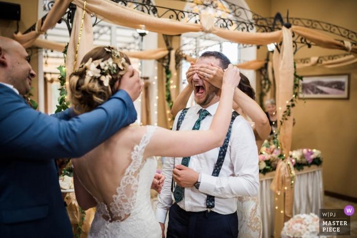 Sesión de boda Lovech con una pareja riendo con los ojos cubiertos por los invitados