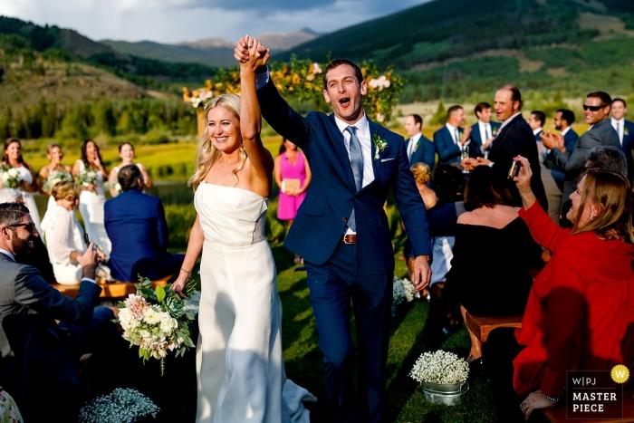 Bride & groom celebrate while receding down the Camp Hale, CO isle.