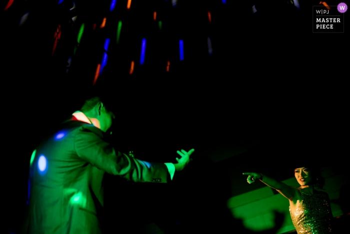 Foto de um casal dançando na recepção sob luzes verdes de DJ por um fotógrafo de casamento top San Jose
