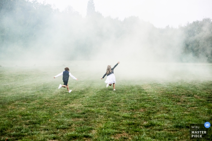 Wedding picture of kids running in field of smoke by Loire-Atlantique photographer