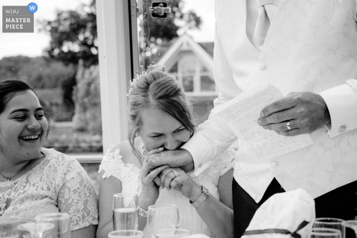 The Hibernia, Hobbs Of Henley Boat Hire wedding photograph of the bride kissing the grooms hand during his speech.