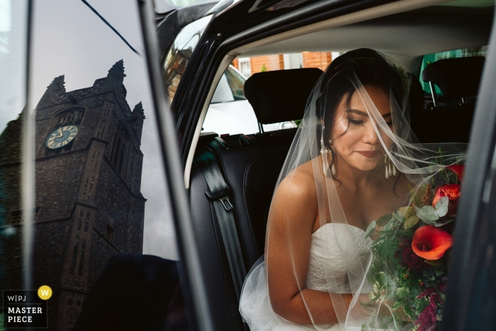 Wedding picture of bride in limo with bouquet by Norfolk photographer
