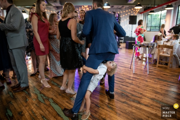 Documentary wedding photography at Baltimore reception of boy hanging on dads leg
