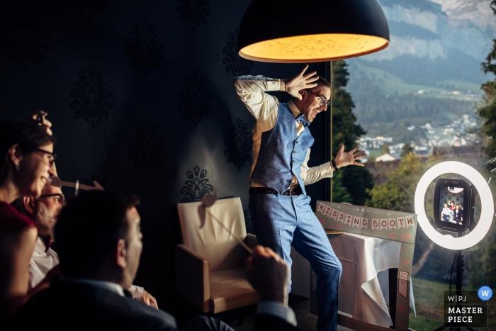 Waldhaus Flims fotografía de boda del novio bailando cerca de una ventana.