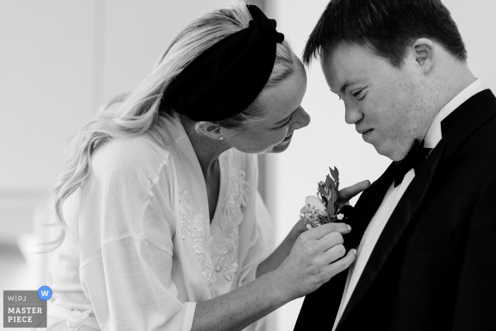 Wedding pictures by Dublin, Ireland photographer of a man having his boutonniere pin on his jacket