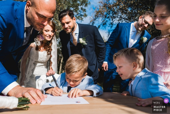 Wedding shot with Zuid Holland couple after their outdoor ceremony with small boys signing the marriage certificate
