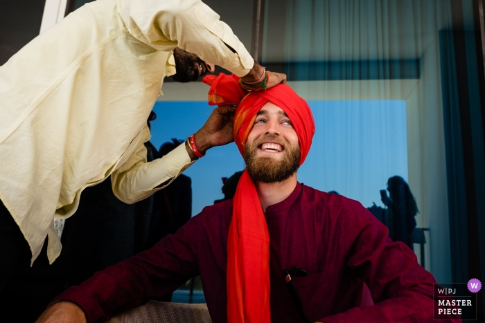 Waldorf Astoria Dubai wedding photo of groom getting headwear fashioned.