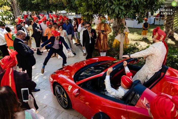 Waldorf Astoria Dubai wedding photo   wedding photograph of the groom arriving in a red convertible Ferrari as men dance before the car