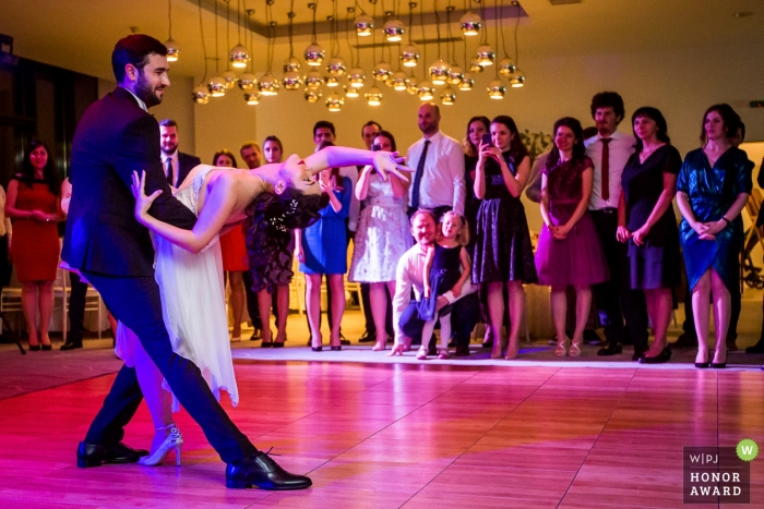 Bucharest couple during their first dance before their guests under pink and purple lights
