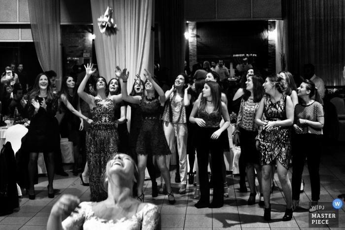 Le photojournalisme de mariage dans la salle de réception à Athènes alors que la mariée lance son bouquet aux femmes célibataires