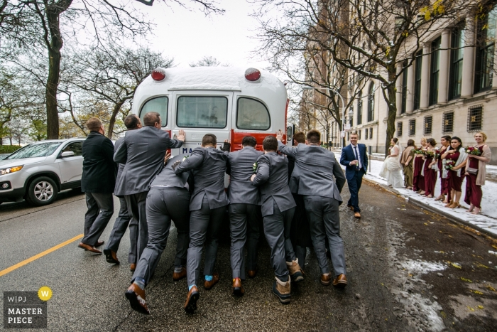 Wedding picture of groomsmen pushing bridal party bus by Chicago photographer