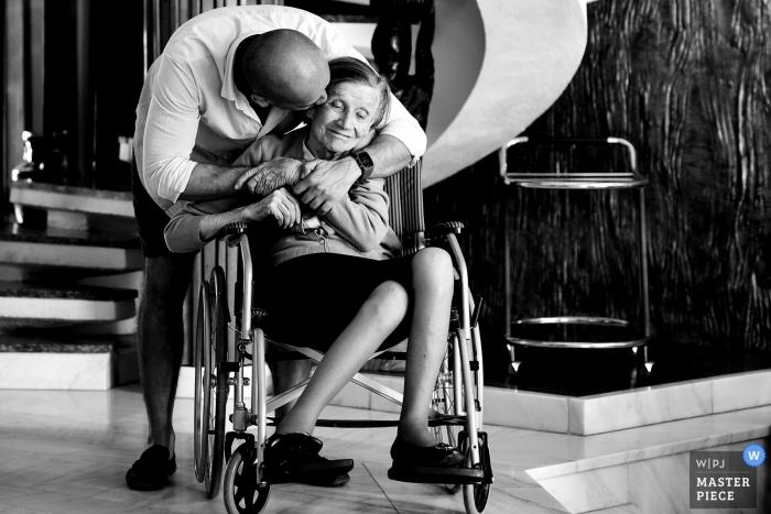 Bucuresti wedding photograph of an elderly woman in a wheelchair receiving a hug and a kiss from a man behind her