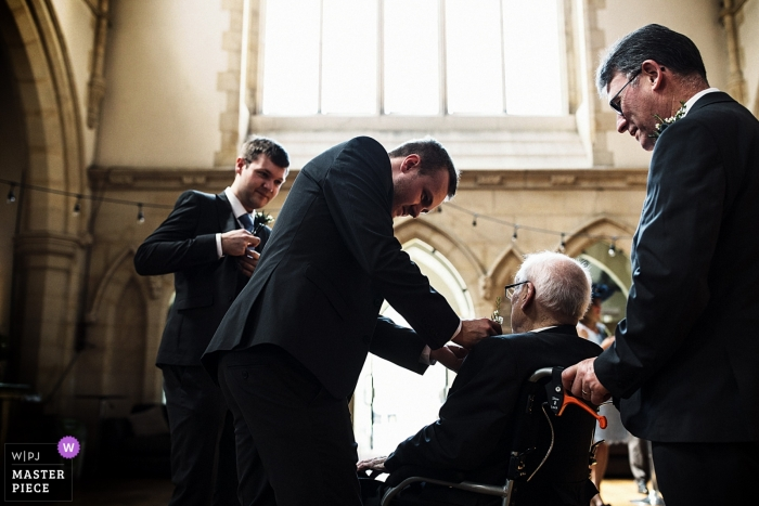 Documentary wedding photograph at Surrey ceremony of man in wheelchair getting help with flowers