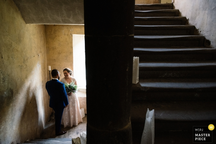 Neidpath Castle, Peebles, Scotland documentary wedding photo of a bride and groom sharing a private moment in the stairwell after the ceremony