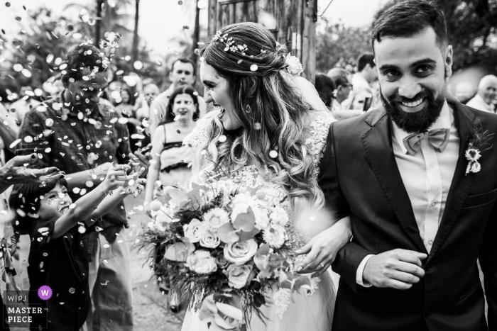Fotos de una pareja saliendo de la iglesia bajo confeti por un fotógrafo de bodas de Río de Janeiro.