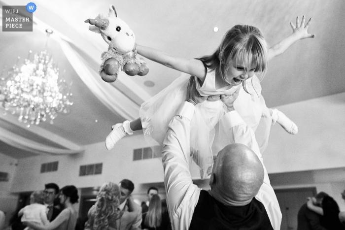 Mythe Barn, Atherstone, BRITISCHE Hochzeitstagphotographie des Blumenmädchens Spaß auf der Tanzfläche habend.