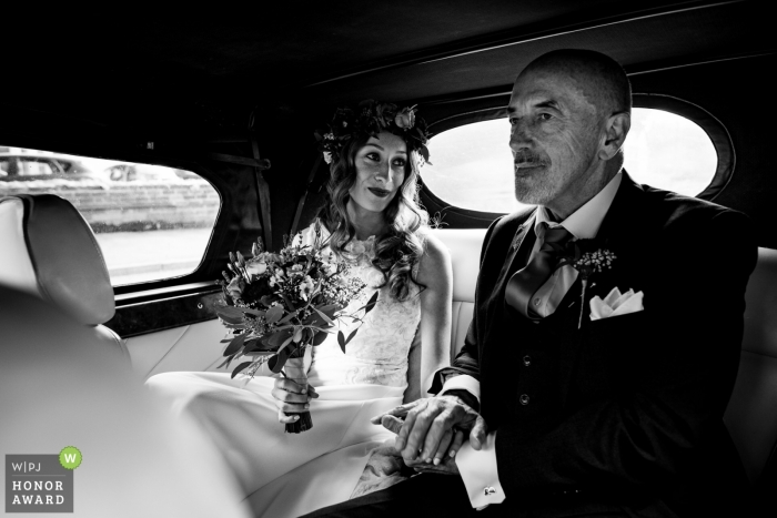 Birmingham, UK  wedding photo | wedding photography of bride with dad in limo holding hands