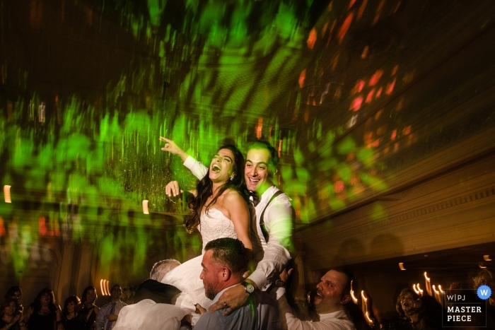 Queens wedding shoot with a couple high above the guests on the dance floor at the reception venue