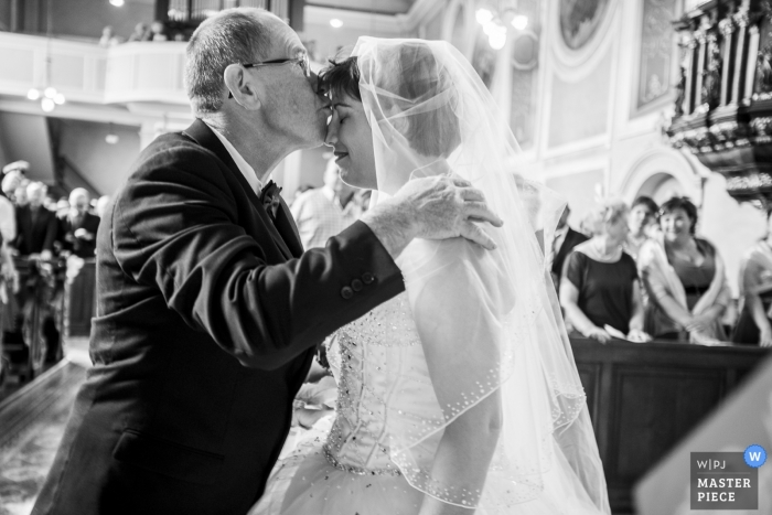 Bouxwiller Documentary wedding photograph of bride getting kissed during ceremony