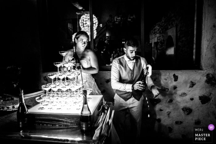 Paris wedding photojournalism image of a couple about to pour champagne into the glass tower
