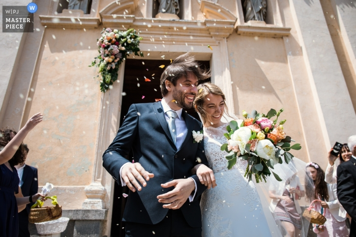 Varese wedding photojournalism image of a bride and groom leaving church under light confetti shower