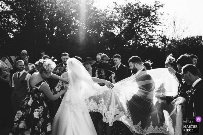 Hochzeitsfotojournalismus der Braut und des Bräutigams, die in den Sonnenschein in Southwold, Suffolk gehen