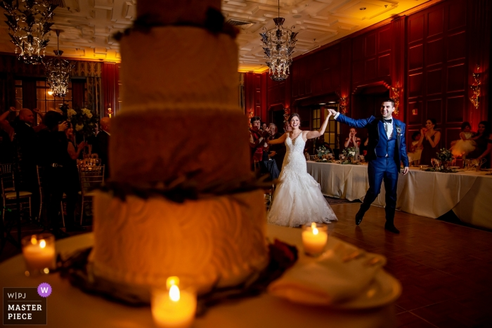 Chicago documentary wedding photo of bride and groom lit during first dance with their cake at Illinois reception