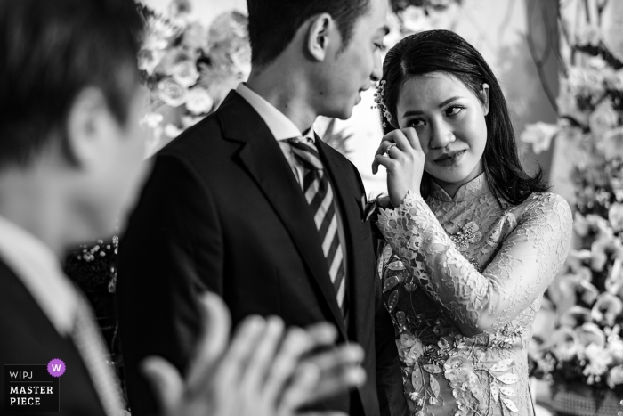 Da Nang wedding photojournalism image of a bride wiping tears during Vietnam ceremony