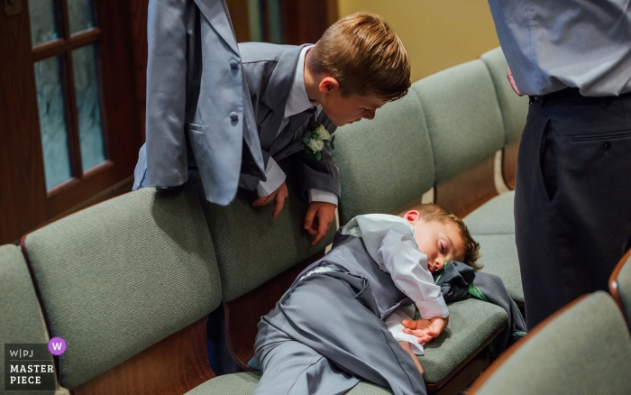 Omaha Wedding Photograph of a ring bearer sleeping during the ceremony