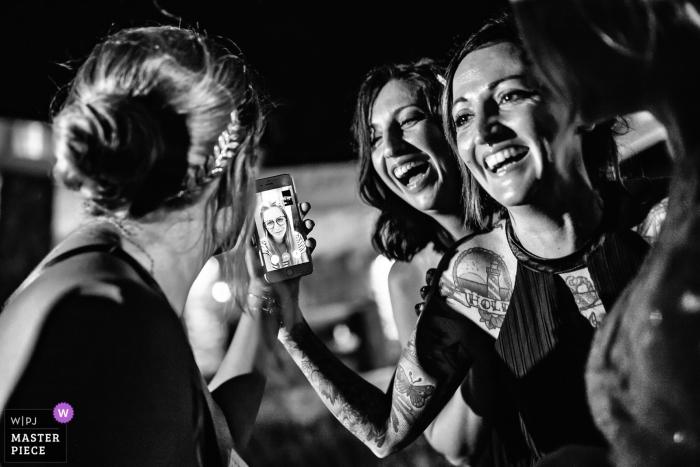 Mykonos, photo de mariage en Grèce d'invités utilisant facetime ou Skype sur un téléphone