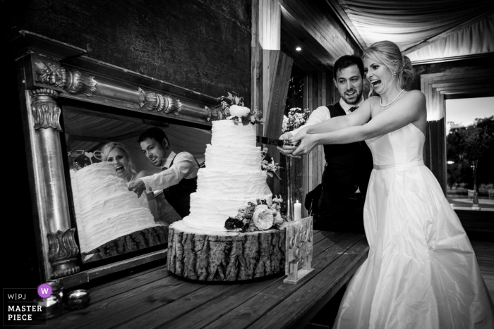 Wedding shoot with Gloucestershire, UK couple cutting their cake with mirror reflection